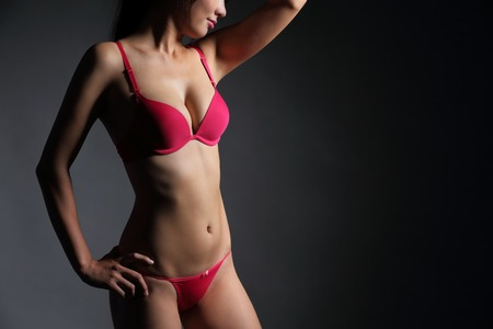 red breast: Attractive Sexy woman with beautiful body posing and wear red underwear isolated on gray background, asian beauty