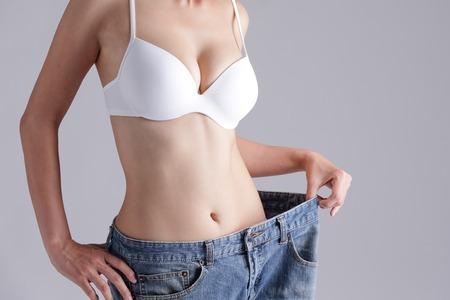 여자는 오래 된 청바지, 아시아 아름다움을 입고 체중 감량을 보여줍니다.