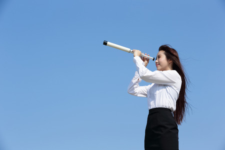 day dream: Business woman with telescope ( spyglass ) looking forward Prospects for future business with blue sky background, asian beauty