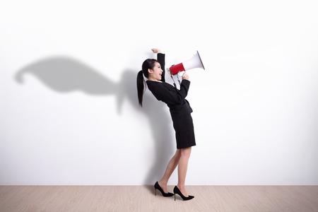 Superheld-Geschäftsfrau, die im Megaphon mit weiße Wand Hintergrund, ideal für Ihr Design oder Text, asiatisch