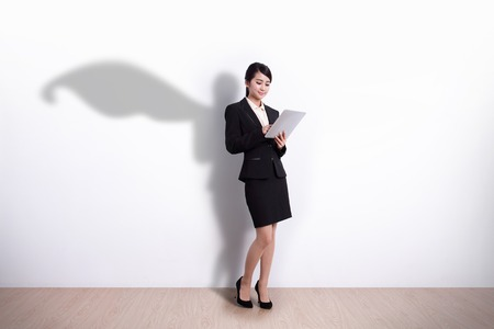shadows: Superhero Business Woman using digital tablet pc computer with white wall background, great for your design or text, asian