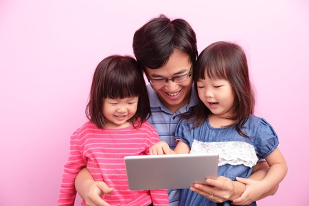 asian men: Happy father and daughter use digital tablet pc isolated over a pink background, asian family