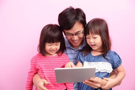 abrazar familia: Padre e hija felices utilizan el PC tableta digital aislado sobre un fondo rosa, familia asi�tica Foto de archivo