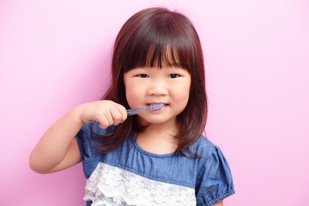 small child: Happy kid girl smile and think something isolated on pink background, asian