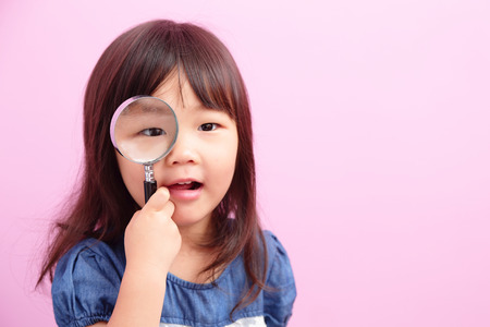 Happy kid girl smile and hold magnifier isolated on pink background, asian photo