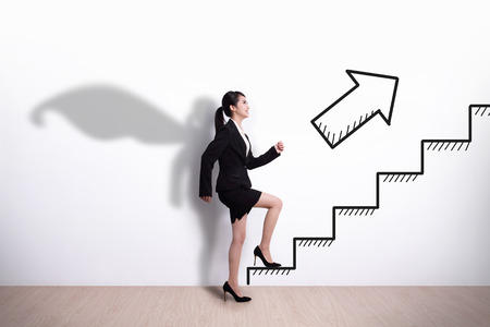 donna ricca: Supereroe Business donna intensificazione sulle scale per ottenere il suo successo con sfondo muro bianco, asiatico