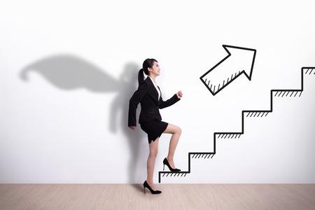 Superhero Zaken vrouw intensivering op de trap naar haar succes met witte muur achtergrond krijgen, Aziatisch