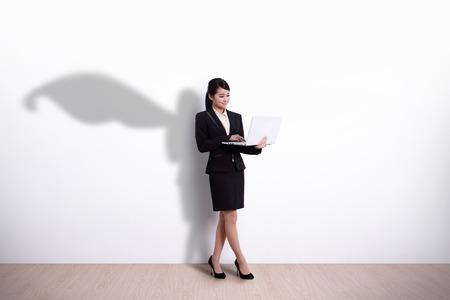 あなたのデザインやテキスト、アジアの偉大な白い壁の背景を持つラップトップ コンピューターを使用してスーパー ヒーロー ビジネス女性