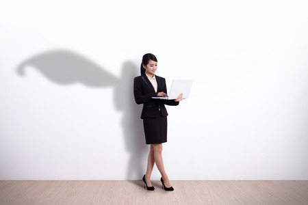 Superhero Business Woman using laptop computer with white wall background, great for your design or text, asian Imagens