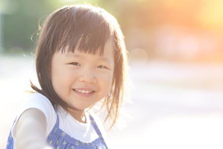 familias felices: Feliz Niña linda en el prado en día de verano, asiático Foto de archivo