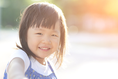 happy families: Happy Cute little girl on the meadow in summer day, asian