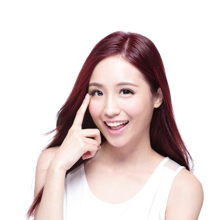 Mujer hermosa sonrisa señalando su ojo con el pelo largo y recto de la salud, el concepto de cuidado de la vista de la salud, asiático modelo de belleza Foto de archivo