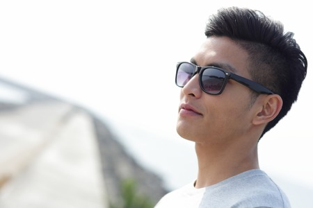 men standing: Fashion young man with his fashionable sunglasses, asian male