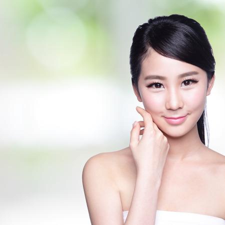 美女: 美麗的皮膚護理的女人臉上露出一絲笑容給你與大自然的綠色背景。亞洲美容
