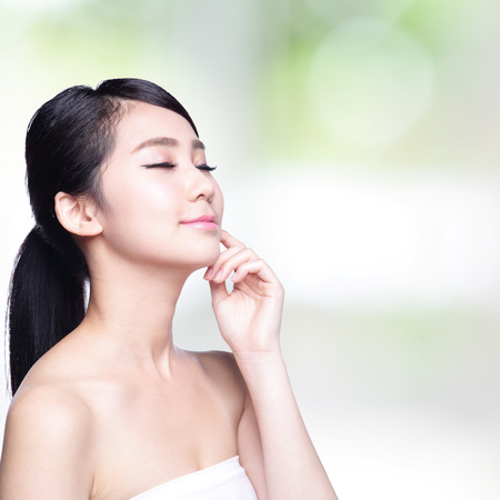 piel: Hermosa mujer de cuidado de la piel de la cara sonrisa y disfrutar sin preocupaciones aisladas sobre fondo de naturaleza verde. Belleza asiática