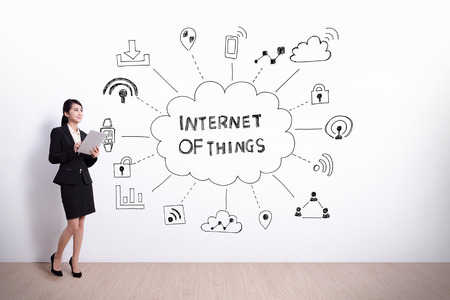 business woman hold computer with drawing internet of things icon and text on white wall background, asian Banque d'images
