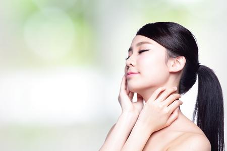 collo: bellezza ritratto di una giovane donna con la mano sulla sua spalla isolato su sfondo verde natura, concetto per la salute, modello di bellezza asiatico