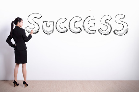 write: business woman write success text with white wall background, asian Stock Photo
