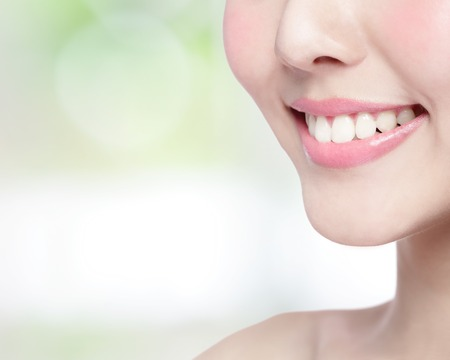 beautiful teeth: Beautiful young woman health teeth close up and charming smile. Isolated on green background, asian beauty