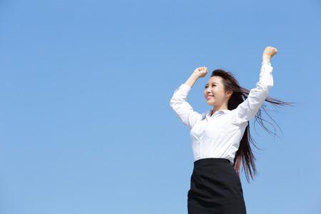 zorgeloze zakenvrouw armen omhoog en voel je vrij geïsoleerd op blauwe hemel achtergrond, Aziatische schoonheid Stockfoto