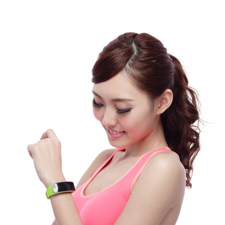 Health sport woman wearing smart watch device with touchscreen doing exercises isolated on white background, asian beauty photo