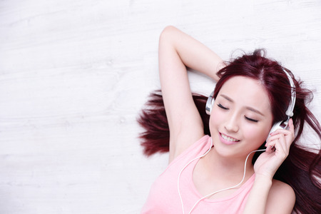 headphones: Young woman enjoying the music and relax lying at home, asian beauty