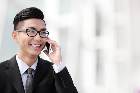 Business man talking on smart phone in the city
