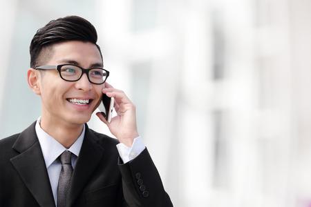 jefe: Hombre de negocios hablando por teléfono inteligente en la ciudad