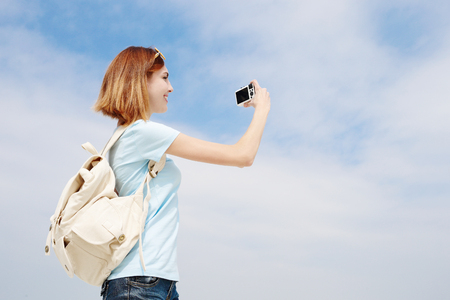 Happy travel woman smile and use camera with sky background, caucasian beauty