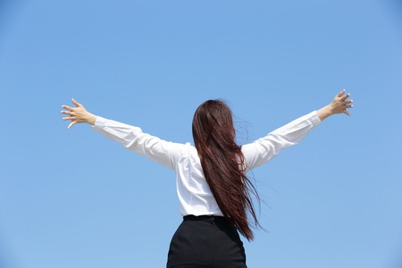 view woman: carefree business woman arms up and feel free isolated on blue sky background, asian beauty