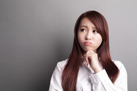 Denken zakelijke vrouw en blik kopie ruimte geïsoleerd op een grijze achtergrond met de vinger op het eerste gezicht, Aziatische schoonheid