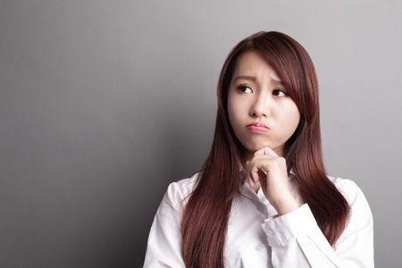 unhappy worker: Thinking business woman and look copy space isolated on grey background with finger at face, asian beauty Stock Photo