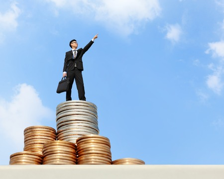 I want be rich - Successful business man stand on money with blue sky, asian male Stock Photo
