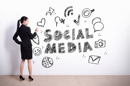 looks: Social Media concept - business woman write social media text and icon on the white wall background Stock Photo