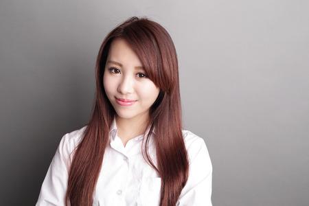 niñas chinas: mujer de negocios confidente sonrisa a usted aislados sobre fondo gris, belleza asiática Foto de archivo