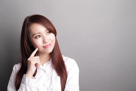 beauty: Denkende Geschäftsfrau und Blick Kopie Raum isoliert auf grauem Hintergrund mit dem Finger auf Gesicht, asiatische Schönheit