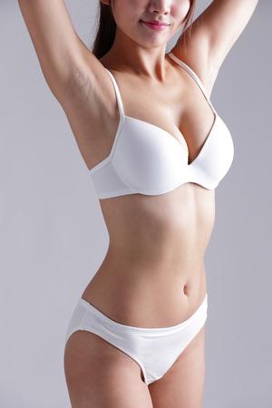 niñas en bikini: Hermoso cuerpo delgado de la mujer aislada en el fondo gris Foto de archivo