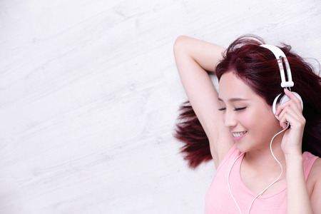 listen music: Young woman enjoying the music and relax lying at home, asian beauty
