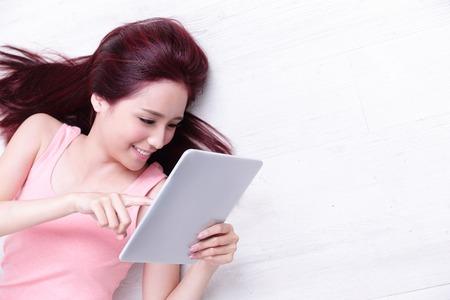 carita feliz: Hermosa mujer joven feliz relajarse tumbado y que usa la PC de la tableta digital, belleza asiática Foto de archivo