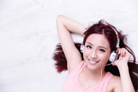 asia people: Young woman enjoying the music and relax lying at home, asian beauty