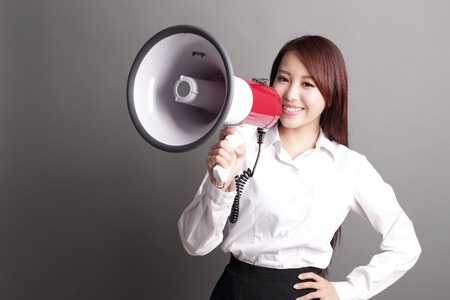 personas comunicandose: Mujer de negocios gritando con un megáfono aislado en el fondo gris, belleza asiática Foto de archivo