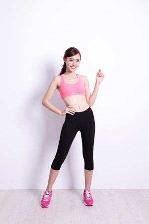 Sport Woman with health figure with white wall background, great for your design or text, asian beauty Stock Photo