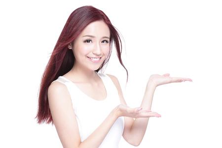 Krása ženy s okouzlujícím úsměvem a ukázat něco pro tebe s zdraví kůže, zuby a vlasy na bílém pozadí, asijských krásy