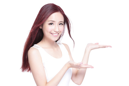 cosmeticos: Mujer de la belleza con una sonrisa encantadora y mostrar algo a usted con la piel de la salud, los dientes y el pelo aislado en fondo blanco, belleza asiática Foto de archivo