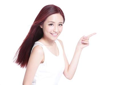 niñas chinas: Mujer de la belleza con una sonrisa encantadora y mostrar algo a usted con la piel de la salud, los dientes y el pelo aislado en fondo blanco, belleza asiática Foto de archivo