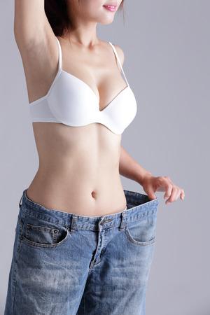 ni�as en ropa interior: mujer muestra la p�rdida de peso con el uso de pantalones vaqueros viejos, belleza asi�tica
