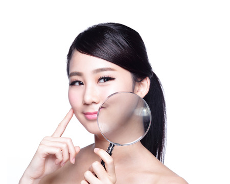 it is isolated: young woman with perfect skin and magnifying glass check it isolated