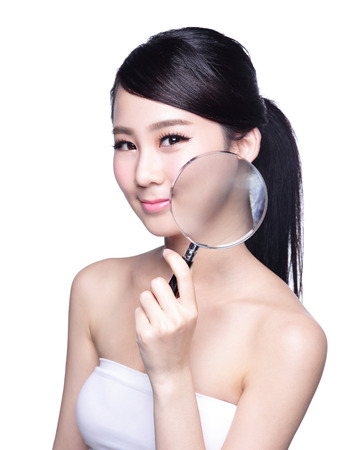 isolated woman: young woman with perfect skin and magnifying glass check it isolated