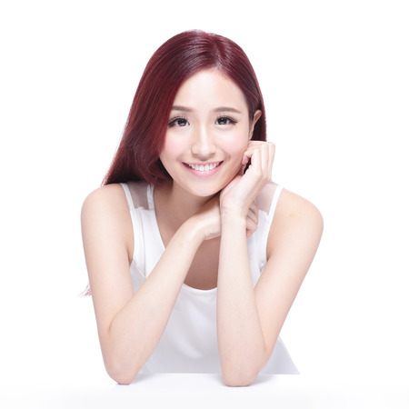 Beauty woman with charming smile to you,  she rests her elbows on white table, she with health skin, teeth and hair, asian beauty