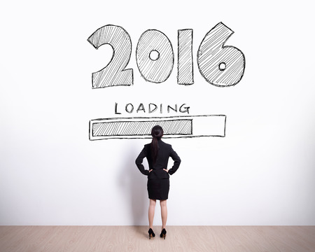 New Year is loading now - Back view of business woman look 2016 text on white wall background Stock Photo